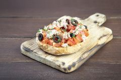 Freselle,or friselle dried bread, italian food. Friselle or Freselle Italian appetizer on wooden board with tomatoes, tuna, garlic,black olives, oregano, salt stock images