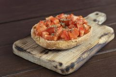 Freselle,or friselle dried bread, italian food. Friselle or Freselle Italian appetizer on wooden board with tomatoes, , garlic,, oregano, salt, and peppercorns royalty free stock photography