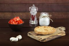 Freselle,or friselle dried bread, italian food. Friselle or Freselle Italian appetizer on wooden board with tomatoes, garlic, salt, and peppercorns. Italian food royalty free stock photo