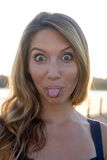 Fresh. A young blond woman sticks her tongue out at you stock photo
