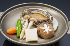 Fresh abalone with mushroom and tofu on frying pan.  Royalty Free Stock Images