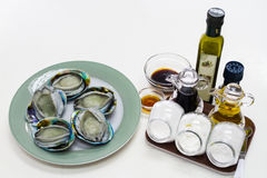 Fresh Abalones with Sauces set. Fresh Abalones with Sauces inlcuded oil and  soy sauce set Royalty Free Stock Image