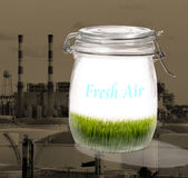 Fresh air in a jar. Covered glass jar containing green grass with a dark industrial photo in the background.  Theme:  Environment and fresh air Royalty Free Stock Photos