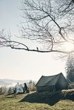 Fresh air and perfect view. Young couple having morning coffee w. Hile sitting near the tent in mountains Royalty Free Stock Images