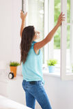 Fresh air. Young woman opening window in living room Stock Photos