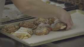 Fresh almond croissants being prepared for sale. View as fresh almond croissants are prepared for sale stock video footage