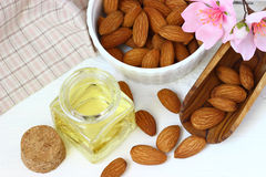Fresh almonds with bottle of oil  and with  flowers. Royalty Free Stock Photo