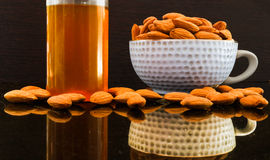 Fresh Almonds and oil. Sweet Fresh Almonds in a cup  oil Royalty Free Stock Photography