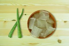 Fresh aloe vera gel on wooden cups and aloe vera leaves on wooden stock photo