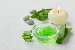 Fresh aloe vera leaf and aloe gel with burning candles on white surface Royalty Free Stock Photo