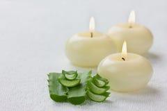 Fresh aloe vera leaf and burning candles on white surface Stock Photos
