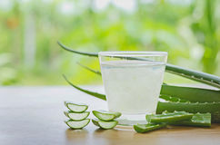 Fresh aloe vera leaves and aloe vera juice in glass on wooden ba. Ckground stock images
