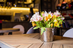 Fresh alstroemeria bouquet in a metal bucket. Fresh beautiful alstroemeria bouquet in a metal bucket on a wooden table in a restaurant royalty free stock photography