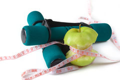 Fresh appetizing apple and brightly colored dumbbells tied with a measuring tape. Diet concept. Stock Images