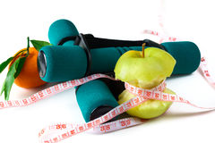 Fresh appetizing apple and brightly colored dumbbells tied with a measuring tape. Diet concept. Stock Photography