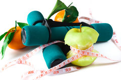 Fresh appetizing apple and brightly colored dumbbells tied with a measuring tape. Diet concept. Stock Image
