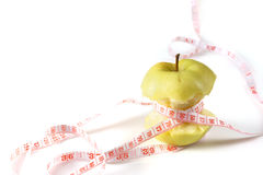 Fresh appetizing apple tied with a measuring tape. White background. Diet concept. Fresh appetizing apple tied with a measuring tape. Slight reflection, white Stock Photos