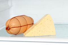 Fresh appetizing sausage and cheese piece on refrigerator shelf. Stock Image