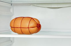 Fresh appetizing sausage on refrigerator shelf. Stock Photos