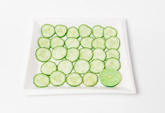 fresh appetizing sliced green cucumbers with lime piece in ceramic plate Royalty Free Stock Photos