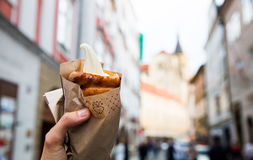 Fresh Appetizing Trdlo or Trdelnik - Traditional National Czech. Tourist holds in hand Trdlo or Trdelnik with ice-cream on the background of city tourist streets royalty free stock photo
