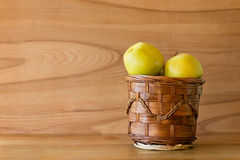 Fresh apple in basket on wooden table Royalty Free Stock Image
