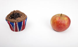 Fresh apple and chocolate cupcake against white background Stock Image