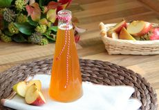 Fresh apple cider. Apple cider with pieces of apple on wooden background Stock Photos