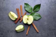 Fresh apple and cinnamon sticks on gray table Stock Photography