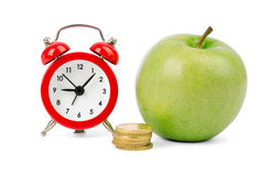 Fresh apple with coins and alarm clock Stock Photography