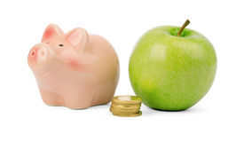 Fresh apple with coins and piggy bank Stock Photos