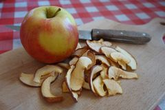 Fresh apple and dried apple slices and knife on wooden chopping board Stock Photos