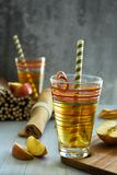 Fresh apple juice in a glass, straw, red apples royalty free stock image