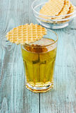 Fresh apple juice in a glass with wafer cookies. On a wooden surface Royalty Free Stock Photo