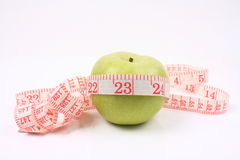Fresh apple with measuring tape Royalty Free Stock Photos