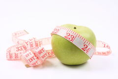 Fresh apple with measuring tape Royalty Free Stock Images