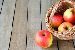 Fresh apple next to a wicker basket Stock Photos