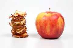 Fresh Apple and a stack of dried Apple slices on white backgroun royalty free stock photos