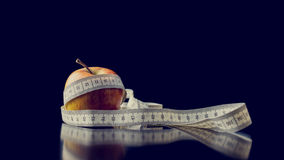 Fresh apple wrapped with a white measuring tape Stock Images