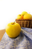 Fresh apples in basket on wooden background and blue napkin Royalty Free Stock Image