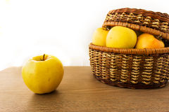 Fresh apples in basket on wooden background Royalty Free Stock Photos