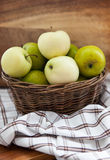 Fresh apples in basket on wooden table Royalty Free Stock Photo