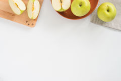 Fresh apples both whole and cut in pieces on wooden board, plate and cloth, on white background with copyspace, top view Royalty Free Stock Photos
