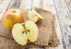 Fresh apples in burlap sack on wooden table background Stock Photo