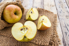 Fresh apples in burlap sack on wooden table background Royalty Free Stock Image