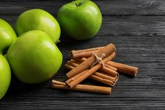 Fresh apples and cinnamon sticks. On wooden table Stock Image