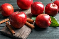 Fresh apples and cinnamon sticks. On wooden table Stock Photo