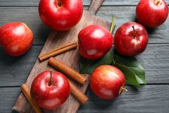 Fresh apples and cinnamon sticks. On wooden table Royalty Free Stock Images