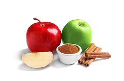 Fresh apples with cinnamon sticks and powder. On white background Stock Images