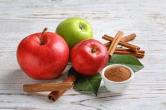 Fresh apples with cinnamon sticks and powder. On wooden table Stock Image
